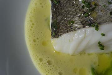 Foto Hake cooked in its own juice with molluscs and parsley